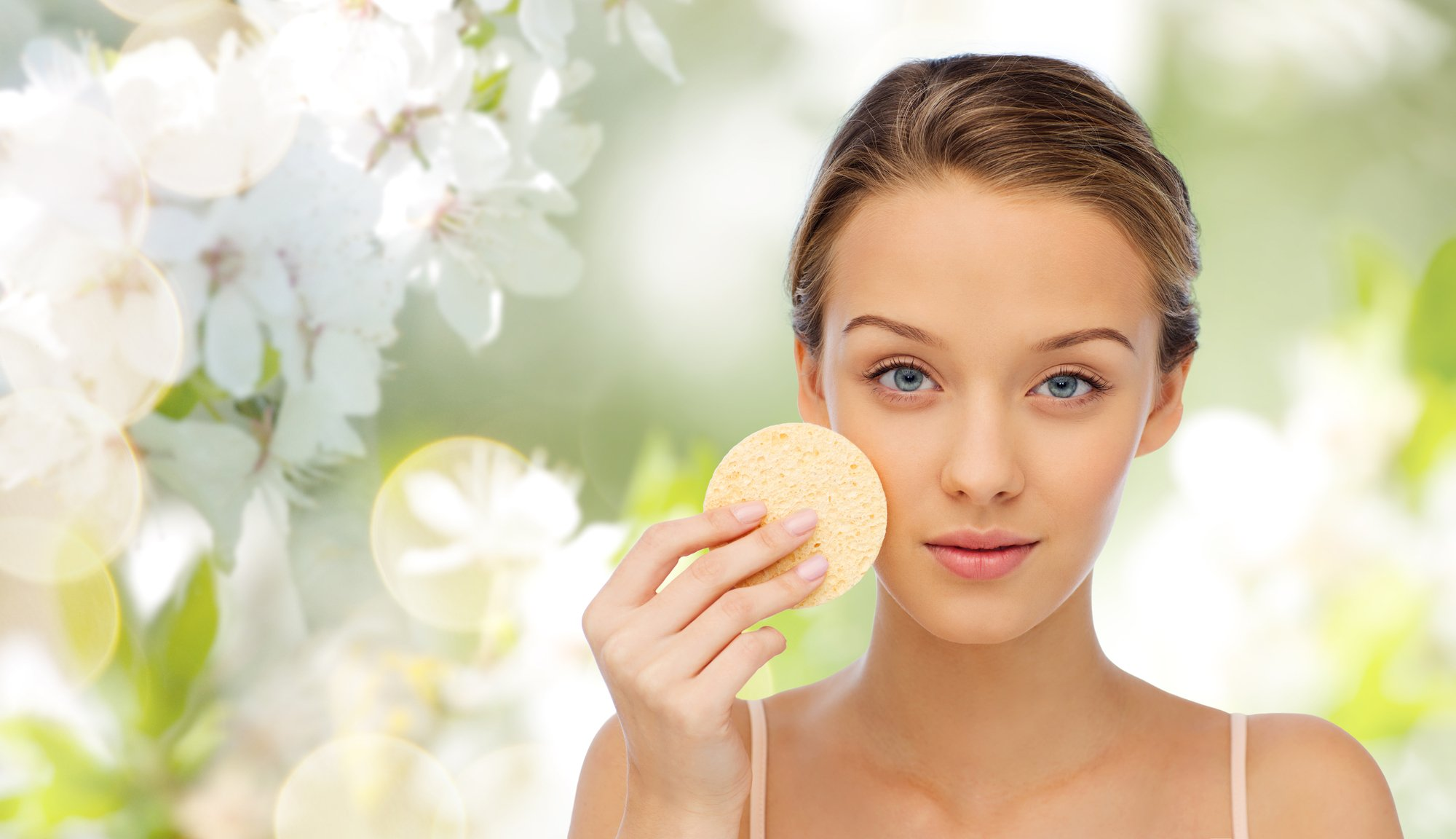 beauty, people, toiletry and skincare concept - young woman cleaning face with exfoliating sponge over cherry blossom background