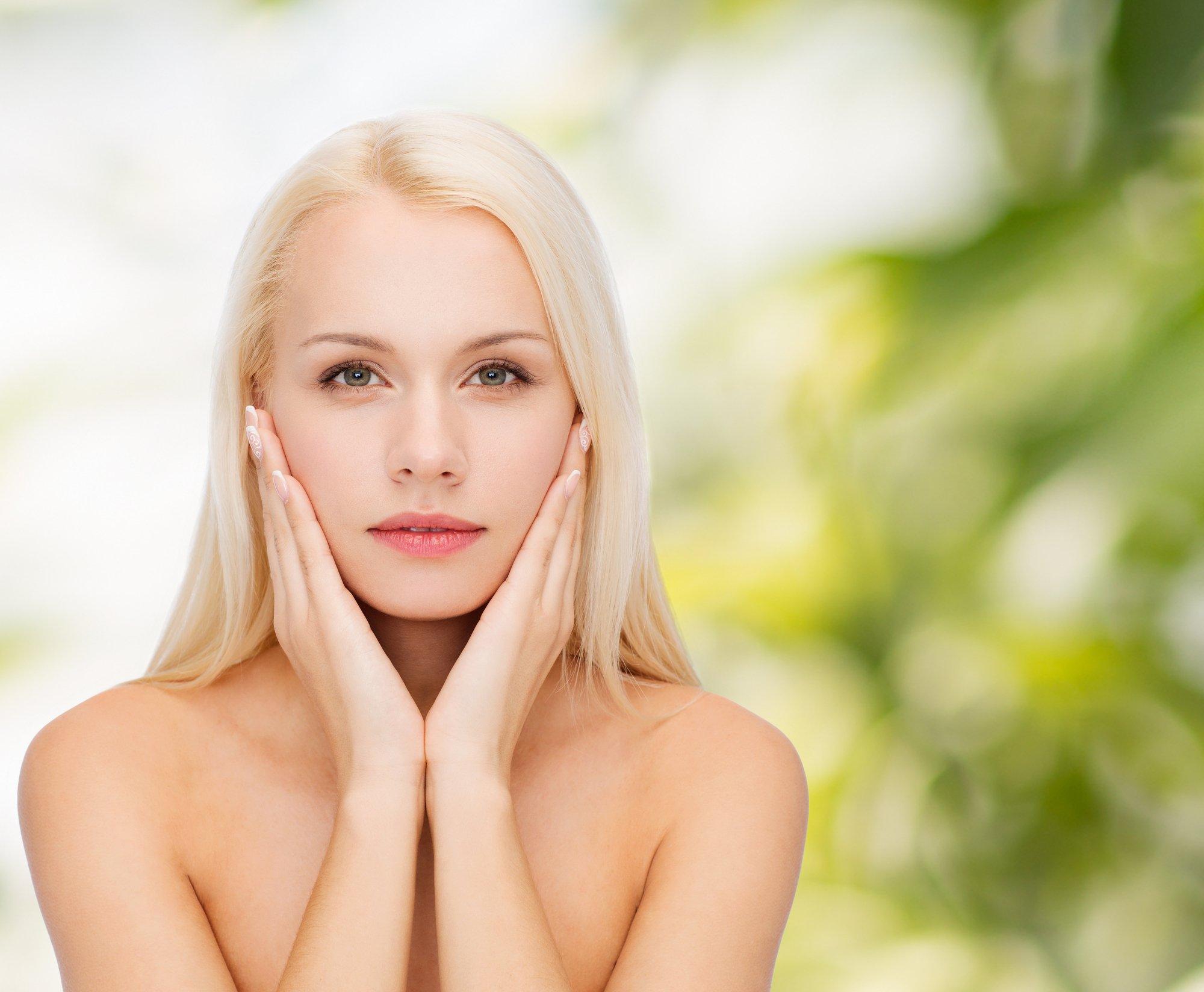 face of beautiful woman touching her face skin