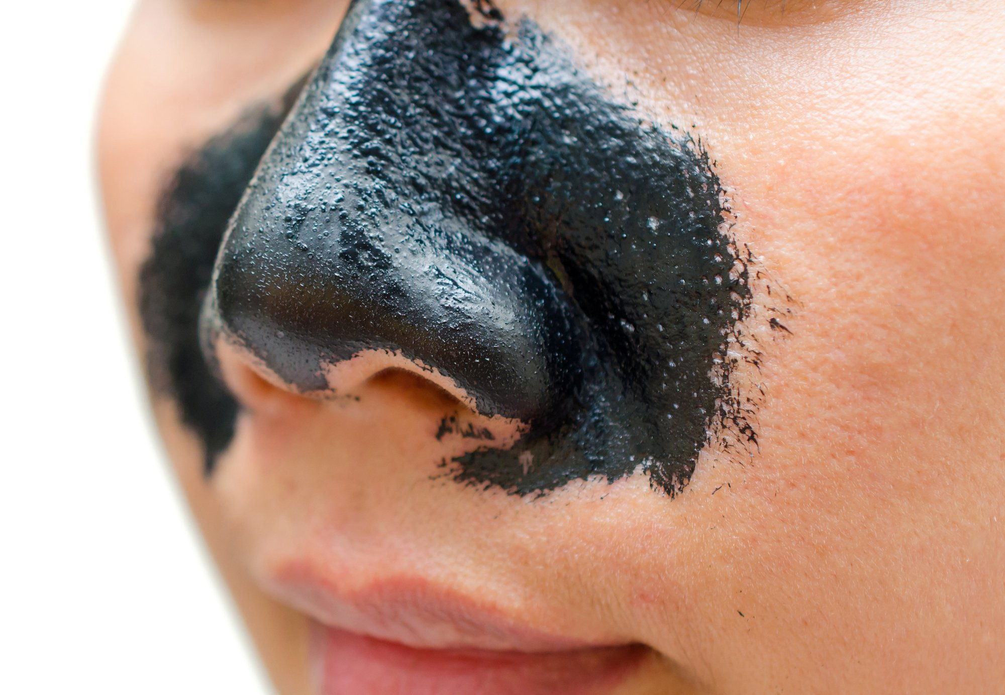 woman applying strips on nose for acne
