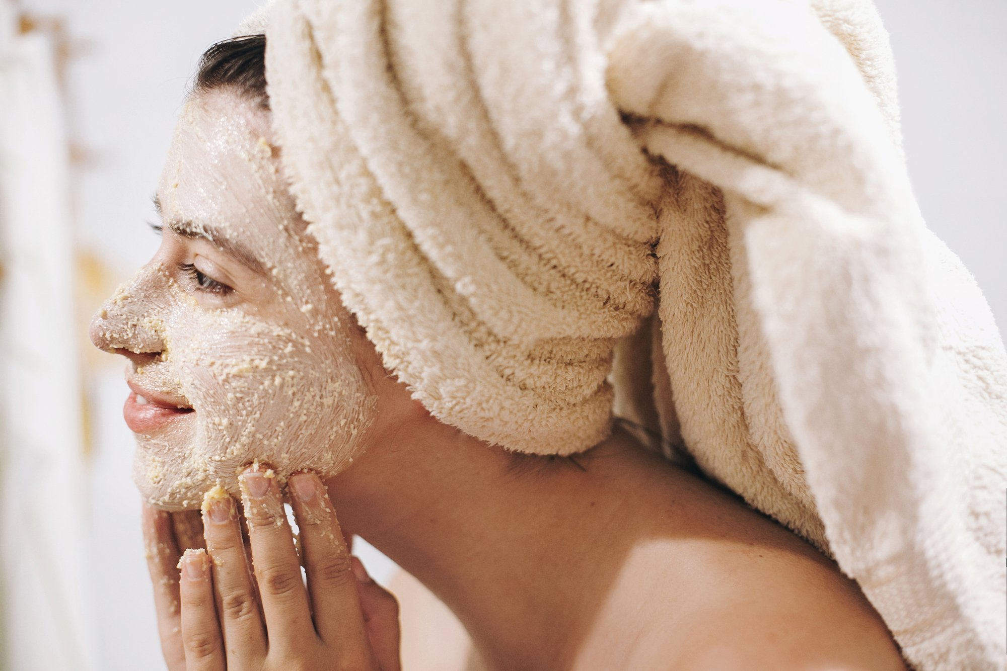 Skin Care concept. Young happy woman in towel making facial mass